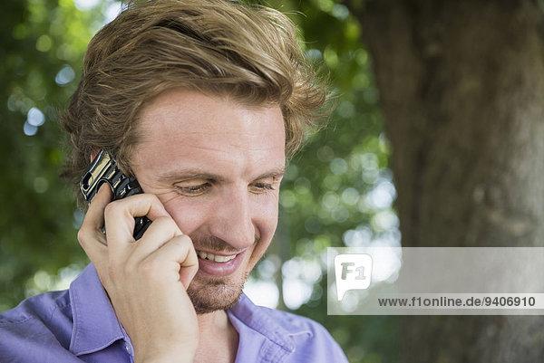Mid adult man talking on smart phone  smiling