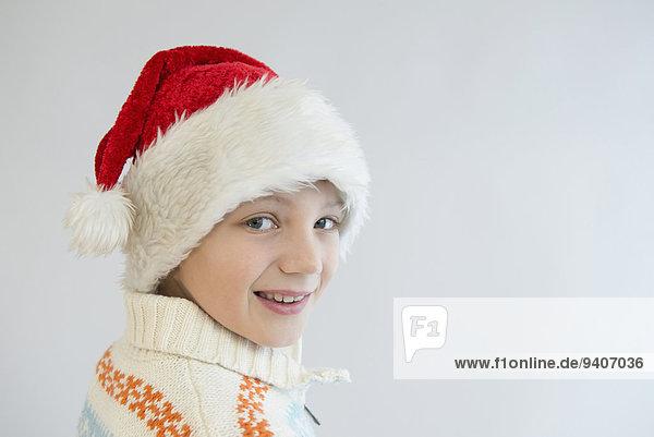 Portrait of boy wearing santa hat against white background  close up