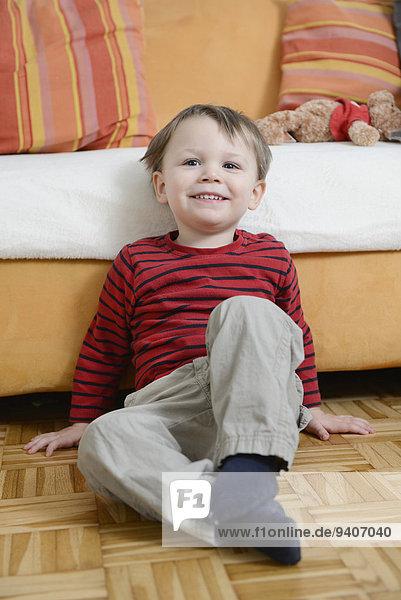 sitzend Boden Fußboden Fußböden lächeln Junge - Person frontal Couch