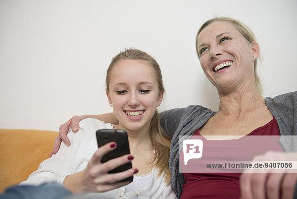 zeigen lächeln Tochter Smartphone Mutter - Mensch