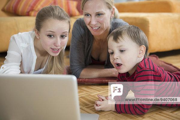 Family using laptop in living room  smiling