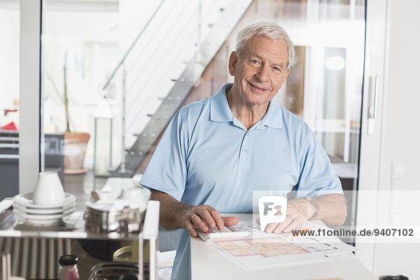 Interior zu Hause Senior Senioren benutzen Mann Taschenrechner lächeln