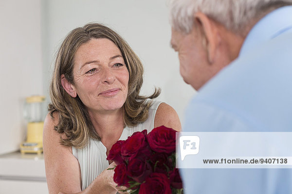 Senior Senioren Frau Mann geben rot Rose
