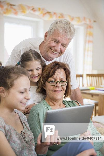 sehen lächeln Großeltern Enkeltochter Tablet PC