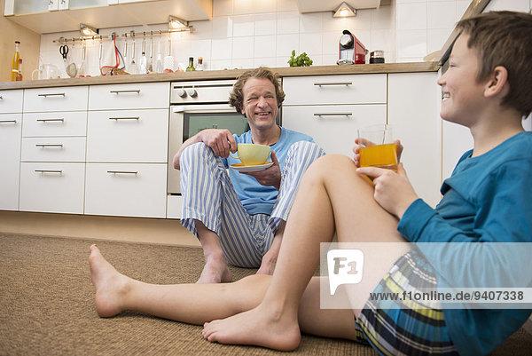 sitzend Fröhlichkeit Boden Fußboden Fußböden Menschlicher Vater Sohn Küche
