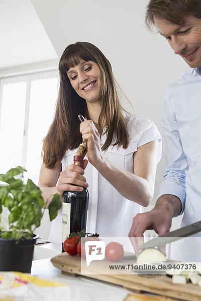 aufmachen Frau Mann lächeln schneiden Wein Gemüse reifer Erwachsene reife Erwachsene Mittelpunkt Erwachsener Flasche