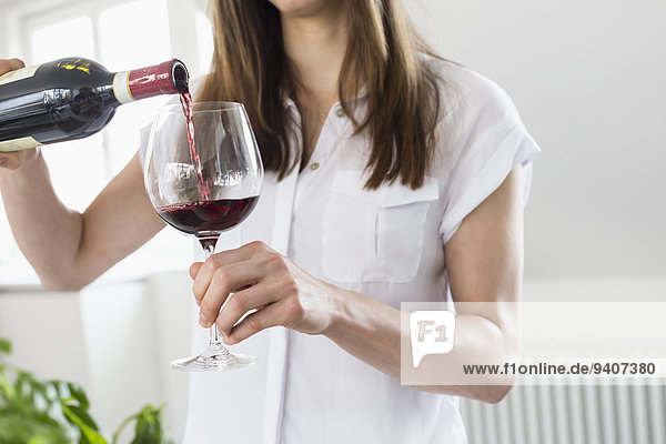 Mid adult woman pouring wine into glass  close up