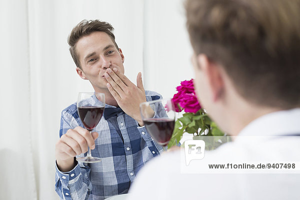 Homosexual couple with red wine