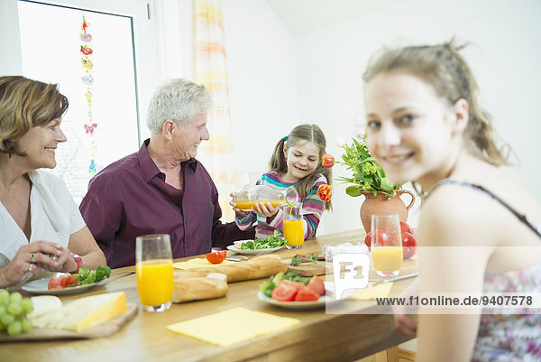 Grandparents and granddaughters sitting at table in living room  smiling