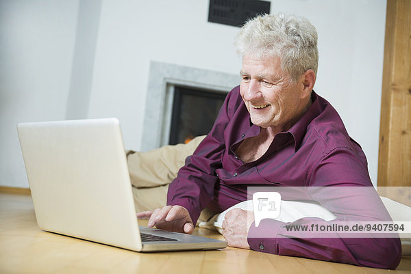 Senior Senioren benutzen Mann Notebook lächeln Zimmer Wohnzimmer