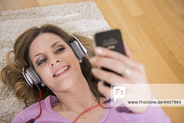 Interior zu Hause Frau zuhören Musik Klassisches Konzert Klassik Smartphone