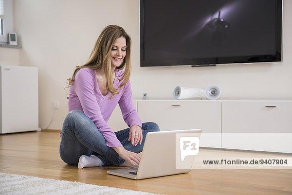 benutzen Frau Boden Fußboden Fußböden Notebook reifer Erwachsene reife Erwachsene