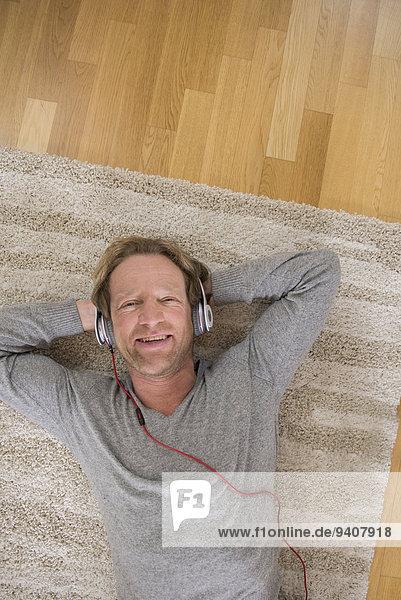 liegend liegen liegt liegendes liegender liegende daliegen Mann zuhören Entspannung Musik Teppichboden Teppich Teppiche Klassisches Konzert Klassik