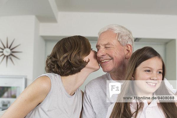 Menschlicher Vater küssen Enkeltochter Tochter Seitenansicht Erwachsener