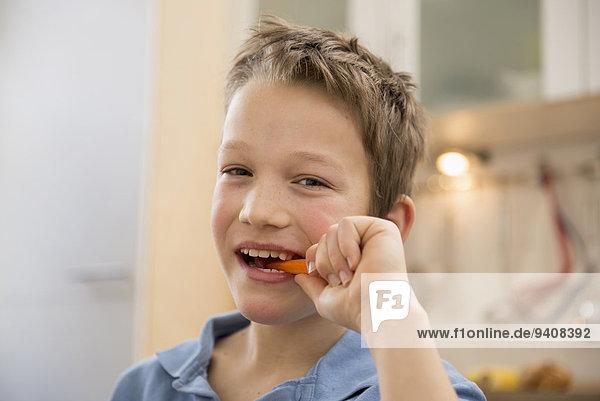 Portrait lächeln Junge - Person Möhre essen essend isst