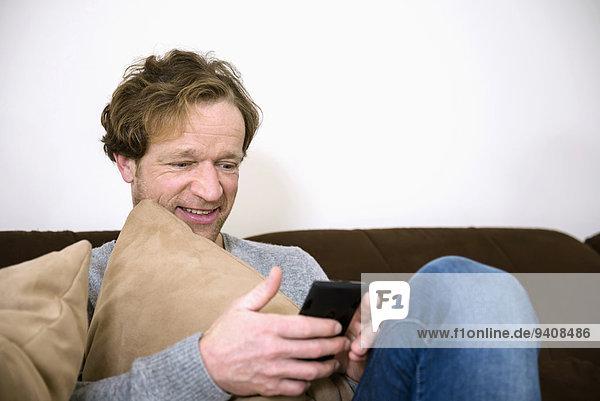 Mann lächeln reifer Erwachsene reife Erwachsene Couch Smartphone
