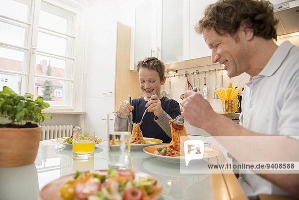Menschlicher Vater Sohn Küche Salat Spaghetti essen essend isst