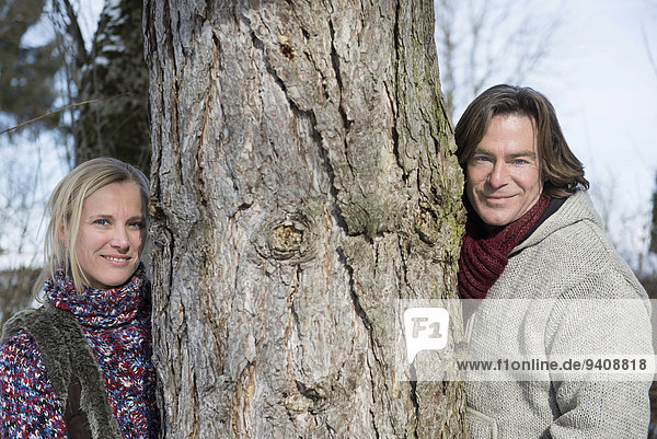 Portrait of couple standing by tree  smiling