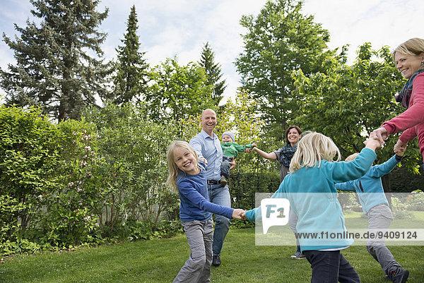 Menschliche Eltern Rasen tanzen Garten