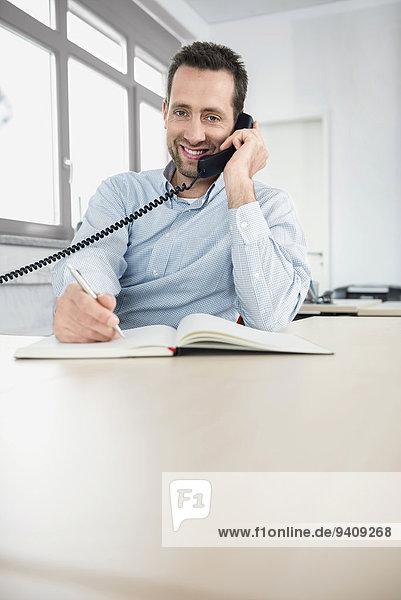 Portrait Mann schreiben Telefon Büro Tagebuch