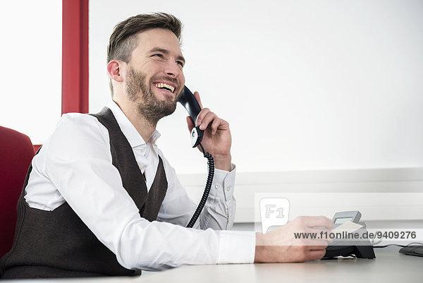 Mann unterhalten lachen Telefon Büro