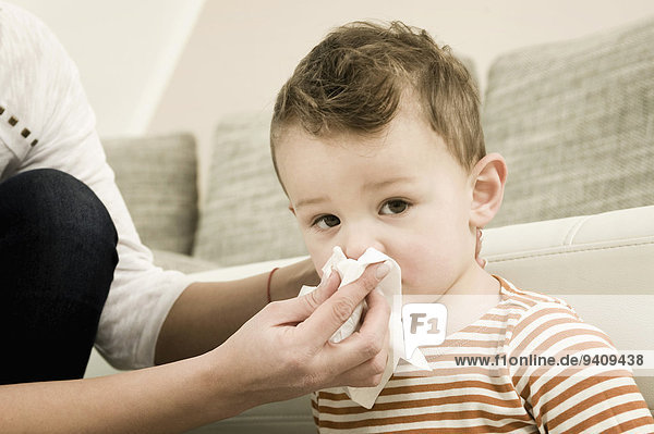 Mother cleaning nose of boy  close up