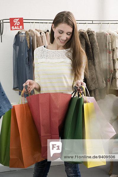 junge Frau junge Frauen lächeln Tasche halten kaufen