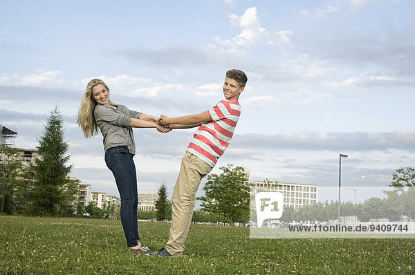 Portrait of teenage couple holding hands in park  smiling