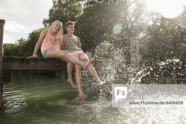 sitzend Wasser Jugendlicher planschen Steg
