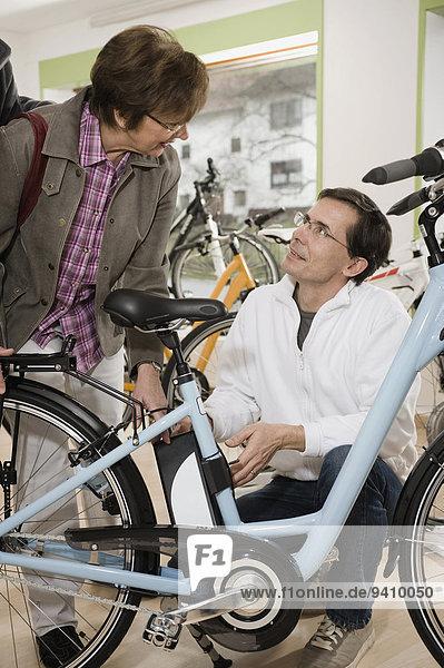nebeneinander neben Seite an Seite Verkäufer Frau sprechen Fahrrad Rad