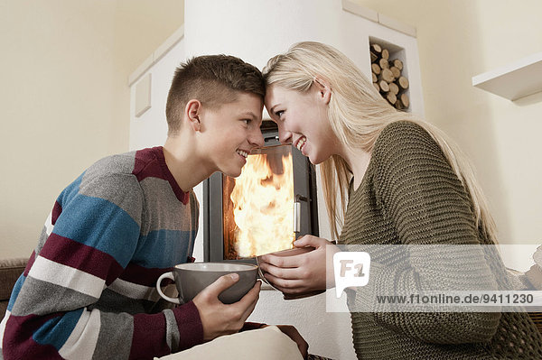 Young teenage couple romantic date log fire
