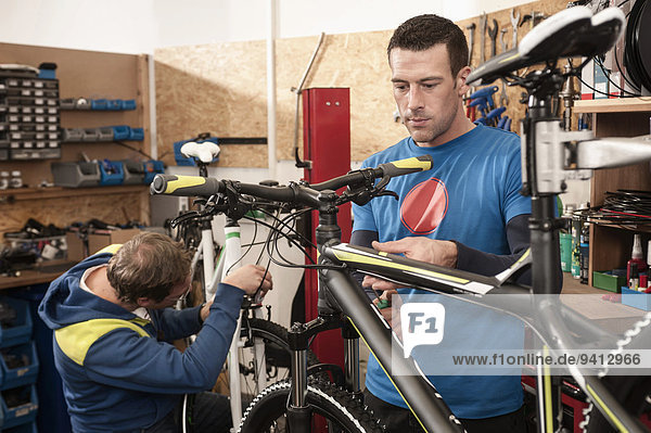 Men repairing bicycle in workshop