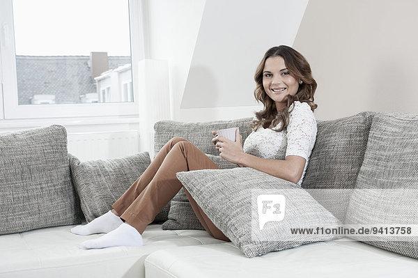 sitzend Interior zu Hause junge Frau junge Frauen Portrait Tasse lächeln Couch