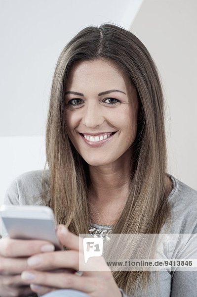Interior zu Hause junge Frau junge Frauen Portrait lächeln Smartphone