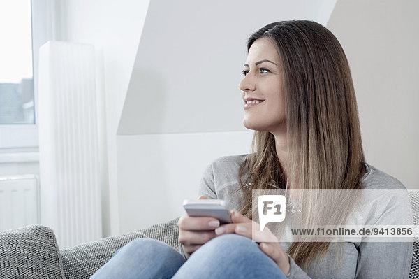 sitzend Interior zu Hause junge Frau junge Frauen Portrait lächeln Couch Smartphone