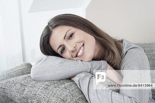 Interior zu Hause junge Frau junge Frauen Portrait lächeln Couch