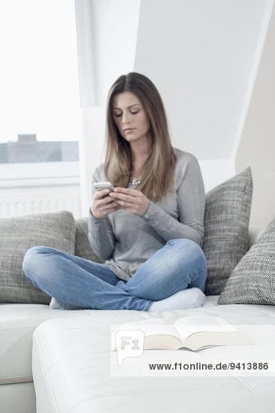 Interior zu Hause junge Frau junge Frauen benutzen Buch offen frontal Taschenbuch Smartphone
