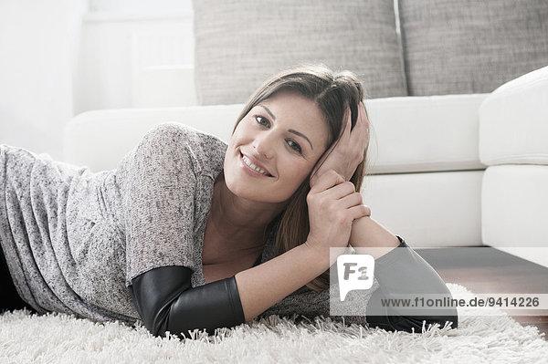 Interior zu Hause junge Frau junge Frauen Portrait Entspannung lächeln Teppichboden Teppich Teppiche