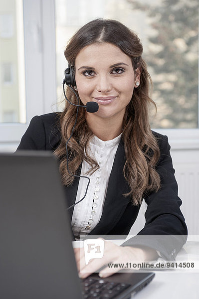 Portrait of young business woman with laptop and headset