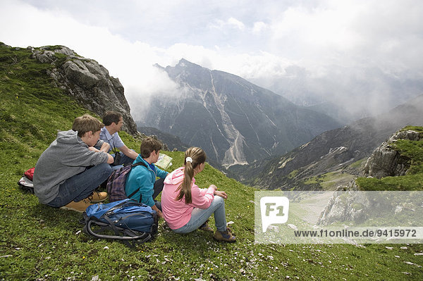 Father and kids looking at hiking map mountains