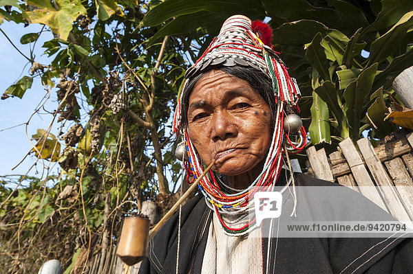 Traditionally dressed elderly woman from the Akha people  hill tribe  ethnic minority  smoking a pipe  portrait  Chiang Rai Province  Northern Thailand  Thailand