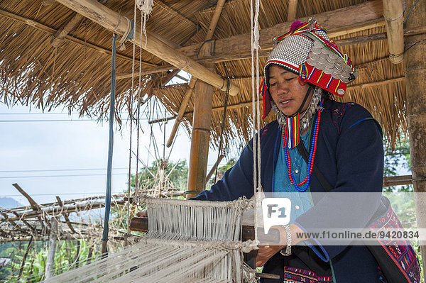 Traditionally dressed woman from the Akha people  hill tribe  ethnic minority  working on a loom  Chiang Rai Province  Northern Thailand  Thailand