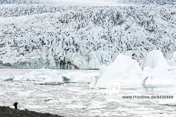 Eisscholle  Eisberge  Gletschersee  Mann fotografiert Gletscherlagune Breiðárlón und Vatnajökull Gletscher  Austurland  Ost-Island  Island