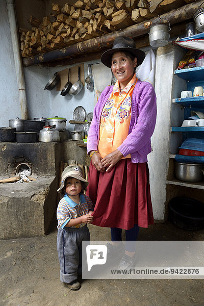 Mother with child in traditional kitchen  Chuquis  Huanuco Province  Peru
