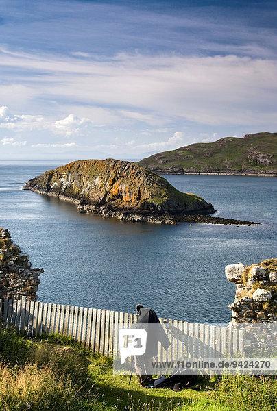 Fotograf auf der Isle of Skye  Atlantik mit Ruine  Schottland  Großbritannien  Europa