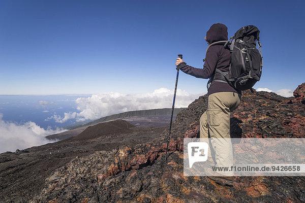 Wanderer auf Gipfel des Vulkans Piton de la Fournaise mit Ausblick auf Wolken und Meer  La Reunion