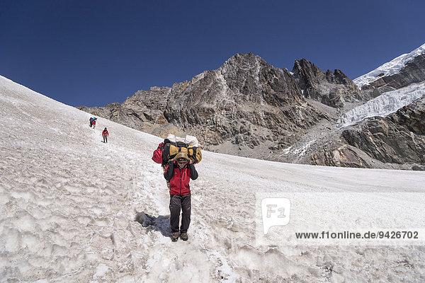 Träger steigt ab vom Cho La Pass über Schneefeld  Khumbu  Solukhumbu  Mount Everest Region  Nepal
