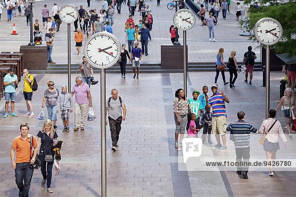 Menschen auf einem Platz mit Uhren  Canary Wharf  Docklands  London  England  Großbritannien
