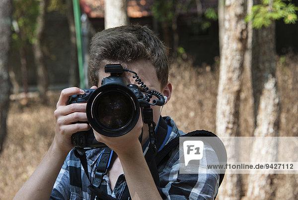 Jugendlicher fotografiert mit professioneller Kamera