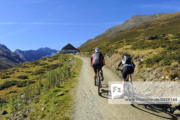 Zwei Mountainbiker auf dem Weg zur Potsdamer Hütte,  Fotschertal mit Ausblick auf die Nordkette,  Tirol,  Österreich